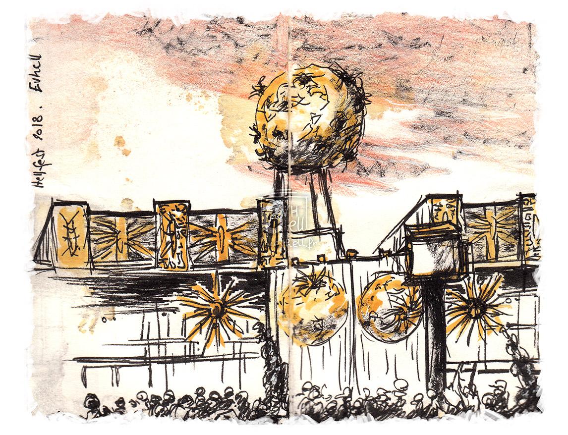 Vue d'horizon du Hellfest, avec ses bâtiments de fer rouillé et cette étrange boule cracheuse de feu la nuit.